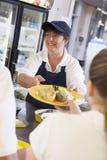 Een vrouwen dienende lunch aan middelbare schoolstudenten stock foto