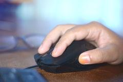 Een vrouwen` s hand die een zwarte muis met behulp van Royalty-vrije Stock Foto