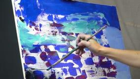 Een vrouwen` s hand doet een borstelslag op het canvas, het langzame motie schieten stock video