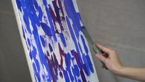 Een vrouwen` s hand is gesmeerd met metaalspatel op het canvas bij het kleurrijke, langzame motie schieten stock videobeelden
