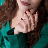 Een vrouwen` s hand met rode spijkers en ringen raakt zacht haar gezicht bij de kin dichtbij de geschilderde steenlippen Close-up royalty-vrije stock fotografie