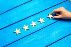 Een vrouwen` s hand zet de vijfde ster De kwaliteitsstatus is vijf sterren Een nieuwe ster, voltooiing, universele erkenning De c royalty-vrije stock afbeeldingen
