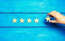 Een vrouwen` s hand zet de vijfde ster De kwaliteitsstatus is vijf sterren Een nieuwe ster, voltooiing, universele erkenning De c stock afbeelding
