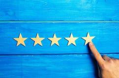 Een vrouwen` s hand zet de vijfde ster De kwaliteitsstatus is vijf sterren Een nieuwe ster, voltooiing, universele erkenning De c stock fotografie