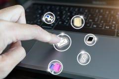 Een vrouwen` s vinger gebruikt een pictogram op Laptop stock afbeelding