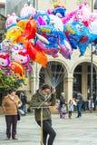 Een vrouwen verkopende ballons bij een straat Stock Foto
