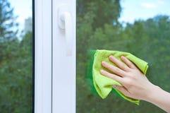 Een vrouwenhand met een vod wast het glazen venster stock afbeelding
