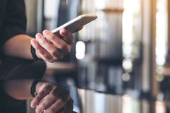 Een vrouwenholding en het gebruiken van smartphone met bezinning over graslijst in bureau stock foto's