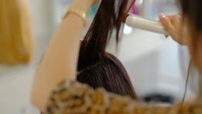 Een vrouwenkapper doet een omvangrijk kapsel aan een cliënt gebruikend een haar ironer, plooiend haar Professionele kapper stock footage