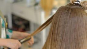 Een vrouwenkapper doet een omvangrijk kapsel aan een cli?nt gebruikend een haar ironer, plooiend haar Professionele kapper stock footage
