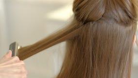 Een vrouwenkapper doet een omvangrijk kapsel aan een cli?nt gebruikend een haar ironer, plooiend haar Professionele kapper stock videobeelden