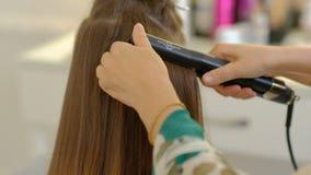 Een vrouwenkapper doet een omvangrijk kapsel aan een cli?nt gebruikend een haar ironer, plooiend haar Professionele kapper stock video