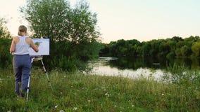 Een vrouwenkunstenaar met een borstel en polytray in haar handen trekt op canvas tegen de achtergrond van aard De kunstenaar trek stock videobeelden