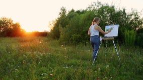 Een vrouwenkunstenaar met een borstel en polytray in haar handen trekt op canvas tegen de achtergrond van aard De kunstenaar trek stock footage