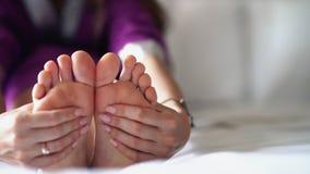 Een vrouwenmassaga de bodem van zijn vermoeide, pijnlijke voet stock video