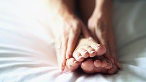 Een vrouwenmassaga de bodem van zijn vermoeide, pijnlijke voet stock footage
