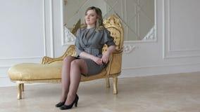 Een vrouwenmodel in grijze kleding zit op de gouden stoel in studio stock videobeelden