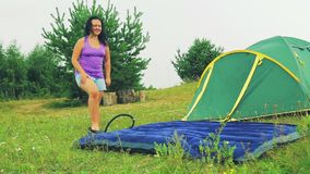 Een vrouwenpompen een opblaasbare matras met haar voet die een pomp gebruiken Tijdoverlappingen stock videobeelden
