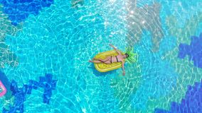 Een vrouwenrust op een matras in een pool stock footage