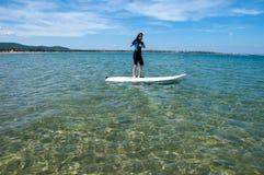 Een vrouwentribune omhoog op een surfplank op het overzees royalty-vrije stock afbeelding
