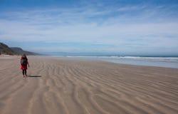 Een vrouwenwandelaar die op een strand met haar rugzak bij het Humpridge-Spoor in Fiordland/Southland in het Zuideneiland lopen i royalty-vrije stock foto's