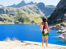 Een vrouwenwandelaar rust dichtbij een bergmeer royalty-vrije stock afbeelding
