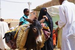 Een vrouwenwhit burqaezels in souk van de stad van Rissani in Marokko worden geparkeerd dat stock foto