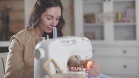 Een vrouwenzitting bij een moderne naaimachine die van ambachten en hobbys genieten stock video