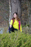 Een vrouwenzitting dichtbij een boom Royalty-vrije Stock Afbeelding
