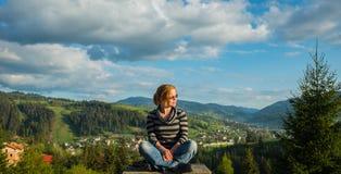 Een vrouwenzitting, die hoog in de bergen rusten op een zonnige dag, de lente, een blauwe hemel en witte wolken op de achtergrond stock fotografie
