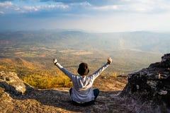 Een vrouwenzitting neer met handen omhoog op rotsachtige berg die uit toneel natuurlijke mening en mooie blauwe hemel bekijken stock foto