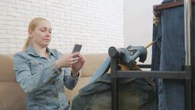 Een vrouwenzitting op een bank onderzoekt en fotografeert, gebruikend een smartphone, een inzameling van denimkleding het hangen  stock footage