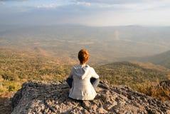 Een vrouwenzitting op rotsachtige berg die uit toneel natuurlijke mening en mooie blauwe hemel bekijken stock afbeelding