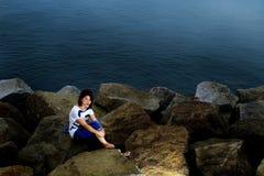Een vrouwenzitting op stenen bij strand Stock Afbeeldingen
