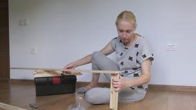 Een vrouwenzitting in een ruimte op de vloer pakt een houten die rek uit in de opslag wordt gekocht Assemblage van meubilair stock video