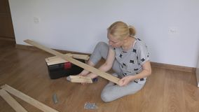 Een vrouwenzitting in een ruimte op de vloer pakt een houten die rek uit in de opslag wordt gekocht Assemblage van meubilair stock footage