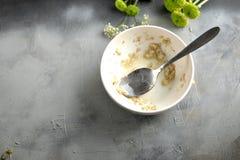 Een vuile plaat met de overblijfselen van voedsel op een grijze achtergrond en een vrije ruimte voor tekst Hoogste mening stock foto's