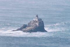 Een vuurtoren bouwt op een rots voort royalty-vrije stock afbeeldingen