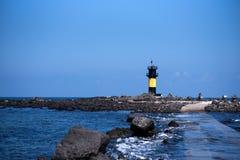 Een vuurtoren op het blauwe overzees stock afbeelding
