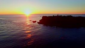 Een vuurtoren op Vreedzame oceaan bij zonsondergang stock video