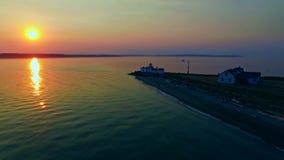 Een vuurtoren op Vreedzame oceaanbaai bij zonsondergang stock footage