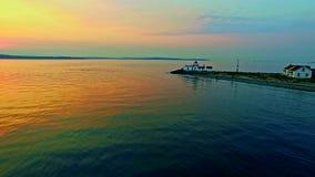Een vuurtoren op Vreedzame oceaanbaai bij zonsondergang stock videobeelden