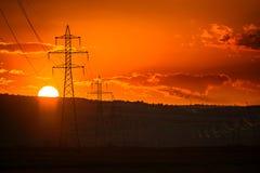Zonsondergang over hoogspanningspijlers stock foto's