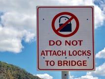 Een waarschuwingsbord die mensen informeren om hangsloten aan een wegbrug niet vast te maken Stock Foto's