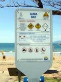 Een waarschuwingsbord die op gevaar van het steken van kwallen, kokosnoten wijzen valt Stock Foto