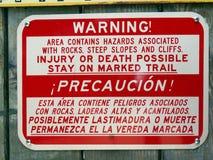 Een waarschuwingsbord op een gebied van zeer steile hellingen en rotsachtige klippen die gevaren voor mensen tonen om voorzorgsma Royalty-vrije Stock Foto's
