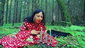 Een waarzegger van de zigeunervrouw in het bos voert magische acties met haar handen uit en blaast uit kaarsen stock videobeelden