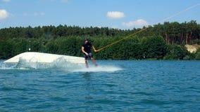 Een wakeboarder glijdt over het water voorbij de camera in een kabelpark Langzame Motie stock video