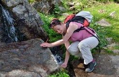 Een wandelaar dichtbij bergbrooklet Royalty-vrije Stock Foto