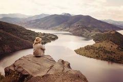 Een wandelend meisje zit op de rand van de klip en het bekijken de rivier en de bergen Plaats: de meanders van Arda-rivier, Bulga Stock Foto's